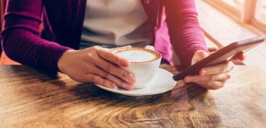 コーヒーを片手にチャットする男性